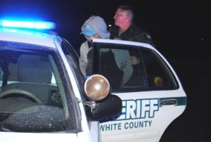 Man involved in White County law enforcement pursuit being placed into custody by White County Sheriff's Department Officer at the intersection of South Mountain and Hayes Street in Smithville at 2:45 a.m. Saturday after the Dodge Neon he was in wrecked and he and a woman tried to get away on foot.