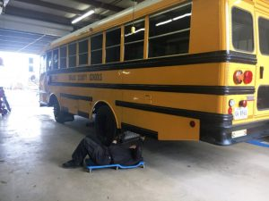 THP Trooper/Inspector Ned Martin checking under bus at school bus garage