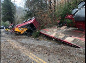 2011 Volvo dump truck pulling a flatbed trailer overturns on Holmes Creek Road