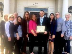 Local Attorney Jeremy Trapp and wife receive Chamber's Community Improvement Award. They are joined by staff, guests, and friends for the special occasion.