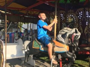 Youngster Enjoying Ride on Merry Go Round at DeKalb County Fair