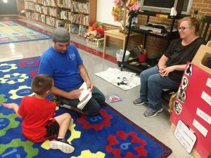 Raymond Lippart, III reading with his son Raymond Lippart, IV with mother Ashley Mooneyham looking on at Smithville Elementary School