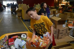 Kolton Slager loads up a wheel barrow with food at Joseph's Storehouse.