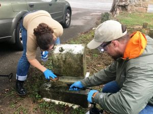 Dr. Stacey Graham (left) Research Professor for the MTSU Center for Historic Preservation, demonstrates proper technique for cleaning tombstone at Smithville Town Cemetery