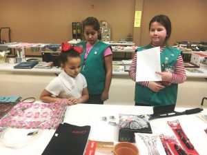 Girl Scouts assist child shopping during regifting event in 2018