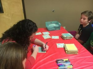 Kids and other volunteers decorate a quilt square during regifting event