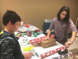 Child getting help wrapping his gift for parents during regifting event