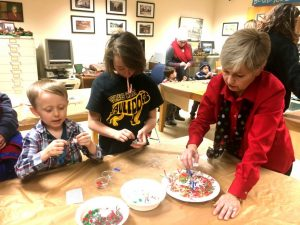 Christmas on the Square 2018: Kathy Hendrixson of Justin Potter Library showing Will and Faith Tripp how to make a Christmas ornament.