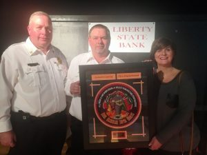 Lieutenant Dusty Johnson was named the 2018 Liberty State Bank Officer of the Year. County Fire Chief Donny Green (left) presented the award Saturday night at the annual banquet. Also pictured is Rhonda Caplinger of Liberty State Bank