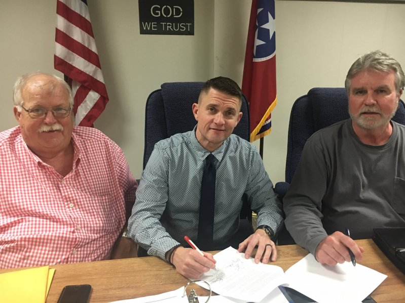 Director of Schools Patrick Cripps signs two year contract extension as approved by the Board of Education Thursday night. Cripps is pictured with the Chairman of the Board W.J. (Dub) Evins, III (right) and Vice Chairman Danny Parkerson