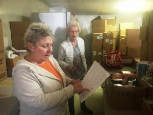 Volunteers Pat Zornow and Sherry Bush reviewing check list at God's Food Pantry (2019 photo)