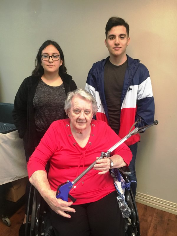 NHC resident Bobbie Ervin receives a pickup tool made by DCHS students Julianna Juarez and Alberto Lucio through the STEM Technology and CTE programs in partnership with NHC Health Care Center of Smithville