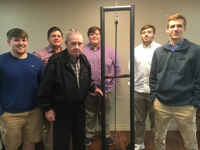 NHC resident , 93 year old Lloyd Tisdale receives a workout machine to help stay in shape made by DCHS students Hunter Fann, Logan Cornelious, Noah Gill, Zach Day, Nathan Atkins through the STEM Technology and CTE programs in partnership with NHC Health Care Center of Smithville