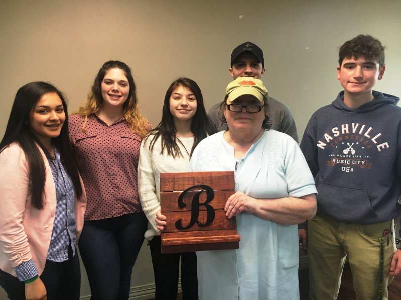 "NHC resident Beth Pittman receives an ipad stand with the initial ""B"" on it made by DCHS students Elvia Rivera, Carrie Mooneyham, Elizabeth Orellana, Justin Gohs, and Conner Rice through the STEM Technology and CTE programs in partnership with NHC Health Care Center of Smithville"