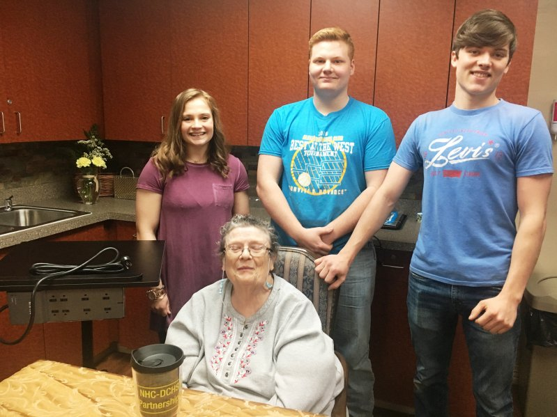 NHC resident Beverly Cripps receives a charging station to keep near her bed for maintaining power to her phone and other electronics  made by DCHS students Haley Chapman, Garrett Driver, and Noah Johnson through the STEM Technology and CTE programs in partnership with NHC Health Care Center of Smithville