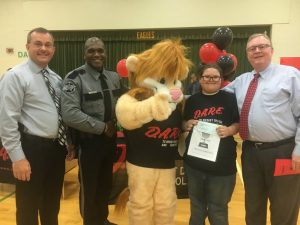 5th Grade DARE Graduation Overall Essay Winner at Northside Elementary School is Olivia Hale pictured with Sheriff Patrick Ray, DARE Officer Lewis Carrick, DARE Mascot DAREN the Lion, and General Sessions/Juvenile Court Judge Bratten Cook, II who presented Olivia a check for $50