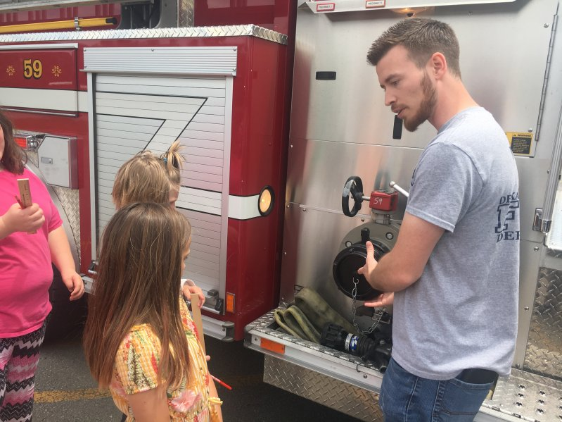 Students attending summer school at Northside Elementary School Tuesday were treated to a visit from members of the DeKalb County Volunteer Fire Department. Matt Adcock, Station Commander of the Belk Station shows the kids how the fire truck operates.
