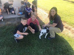 DeKalb Animal Shelter Director Megan Moore shows off puppy to DeKalb West 2nd graders