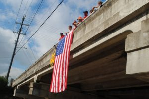 Local firefighters last year greeted motorcycle riders with waves and a huge American flag from the Veteran's Memorial bridge on College Street overlooking the route below on Broad Street.