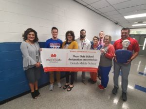 The DeKalb County School District has been designated a Project ADAM Heart Safe School District. DeKalb Middle School staff being presented with their Heart Safe School designation banner