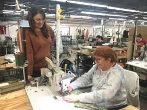 Amanda Callis, Plant Manager of 620 Pelham, Inc (formerly Omega Apparel) with employee Estelle Sanchez who is shown sewing military waterproof Goretex seam sealed Parka trousers for the US Navy
