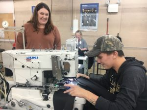 Amanda Callis, Plant Manager of 620 Pelham, Inc (formerly Omega Apparel) with employee Brittney McCardell who is shown sewing button holes on the Broadfall pants for the US Navy