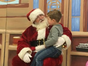 Santa visits with youngster on the North Pole Stage during Festival of Trees 2nd Annual Opening Night,