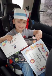 Head Start student Bucksley Haney receives his diploma, cap, and perfect attendance certificate during drive through Head Start Graduation Wednesday