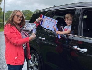 LBJ & C Smithville Head Start Director Cathy Shehane presents ribbons and certificate to head start student Bucksley Haney during Drive Through Head Start Graduation Wednesday