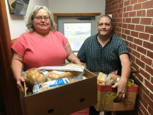 Snow Hill Baptist Church carries on 20 year mission to feed the needy. Snow Hill Baptist Church member Patty Hale and Pastor Todd Pack preparing food boxes for church food ministry distribution