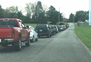 Those being served by the Snow Hill Baptist Church Food Ministry Sunday began lining up in their vehicles on Snow Hill Road near the church an hour before the scheduled drive thru pickup began
