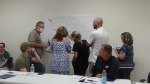 Members of the redistricting committee looking over county map showing the existing seven districts and the proposed changes